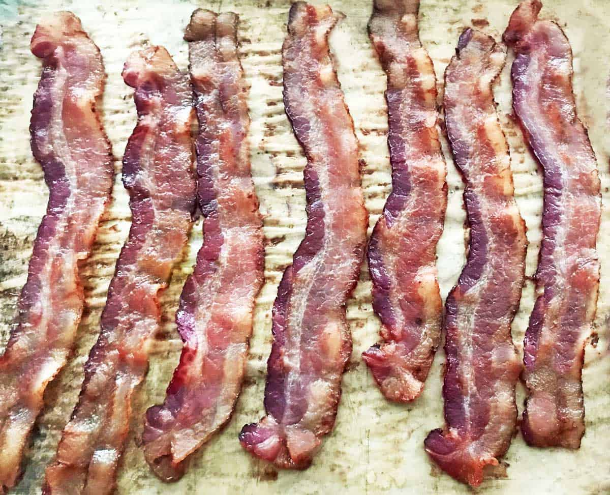 7 slices of oven cooked thick cut bacon on parchment paper.