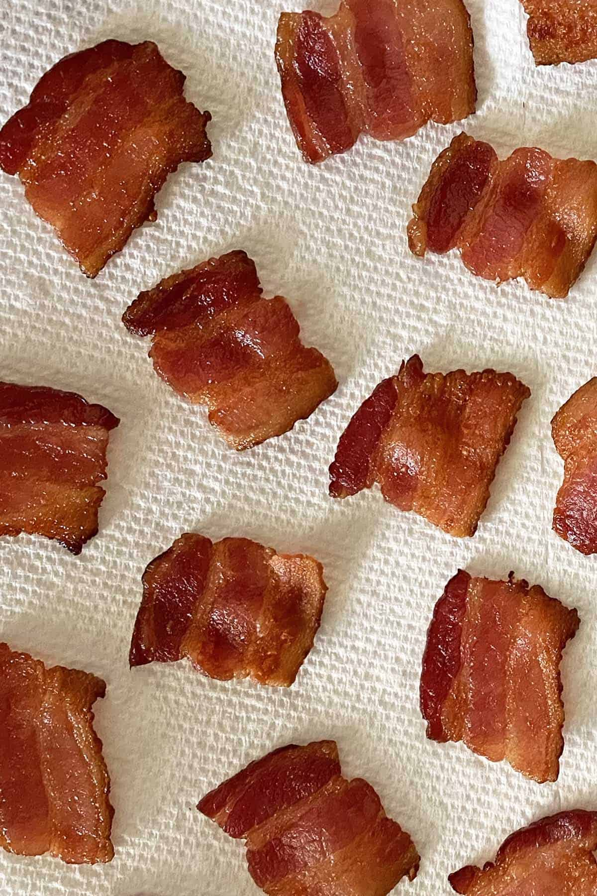 13 cooked squares of bacon draining on white paper towwels.