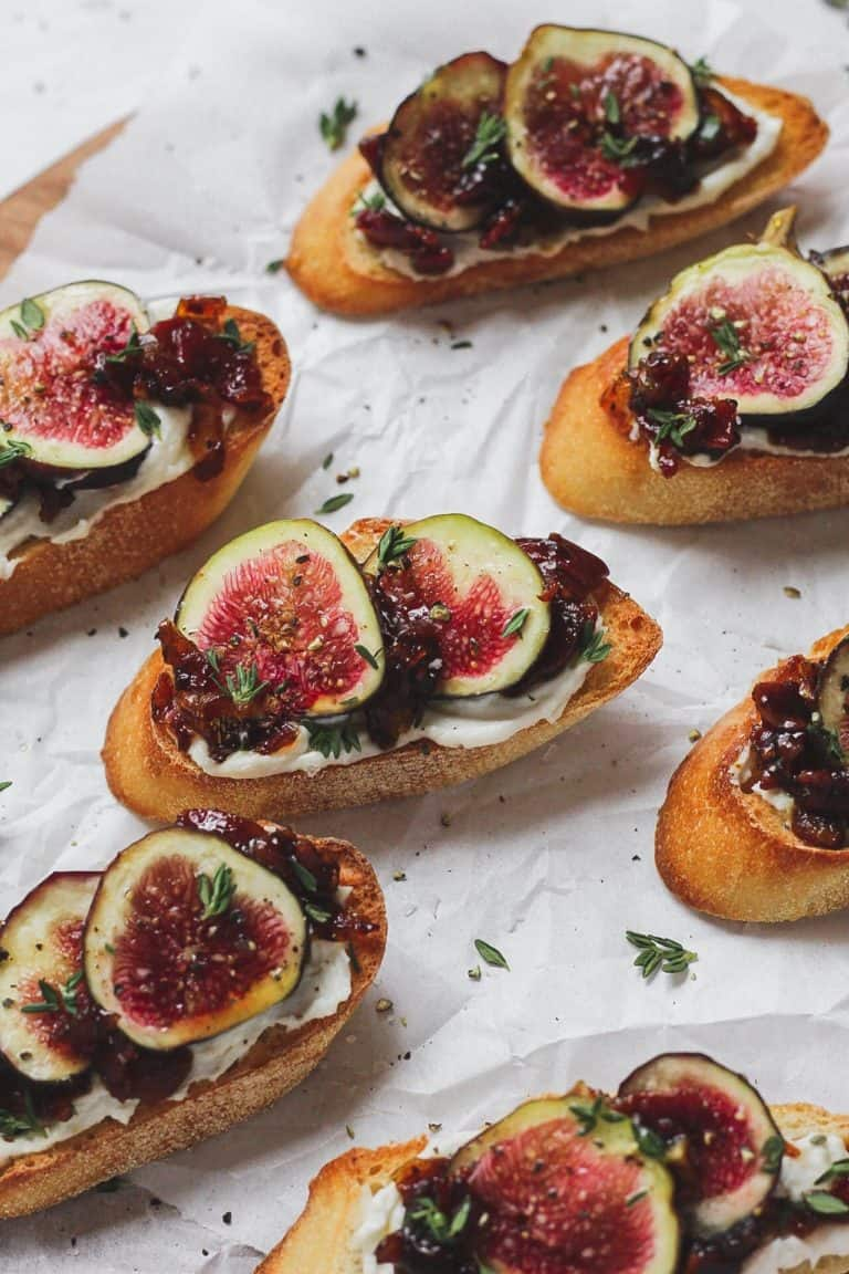 6 pieces of fig and bacon jam crostini on a white background