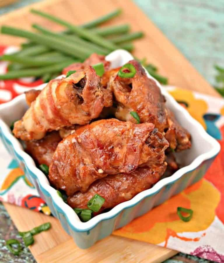 square dish with 4 bacon wrapped chicken wings on a colorful towel with scallions in the background