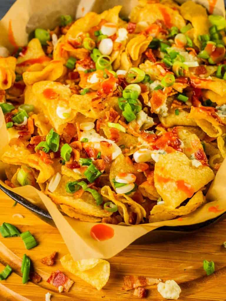 Close up of a platter piled with loaded chips with blue cheese and bacon