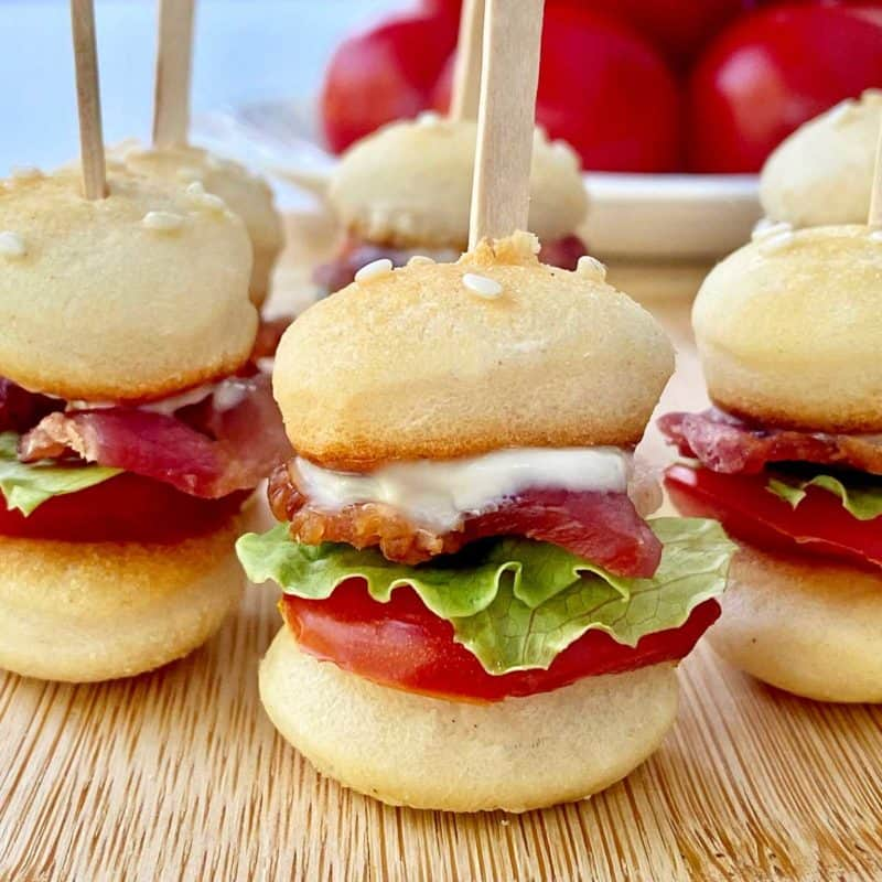 Closeup of 5 mini BLT sliders on skewers resting on a bamboo cutting board, with a bowl of tomatoes in the background