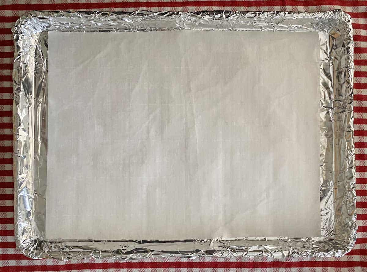 A baking sheet covered with aluminum foil and topped with a sheet of white parchment paper