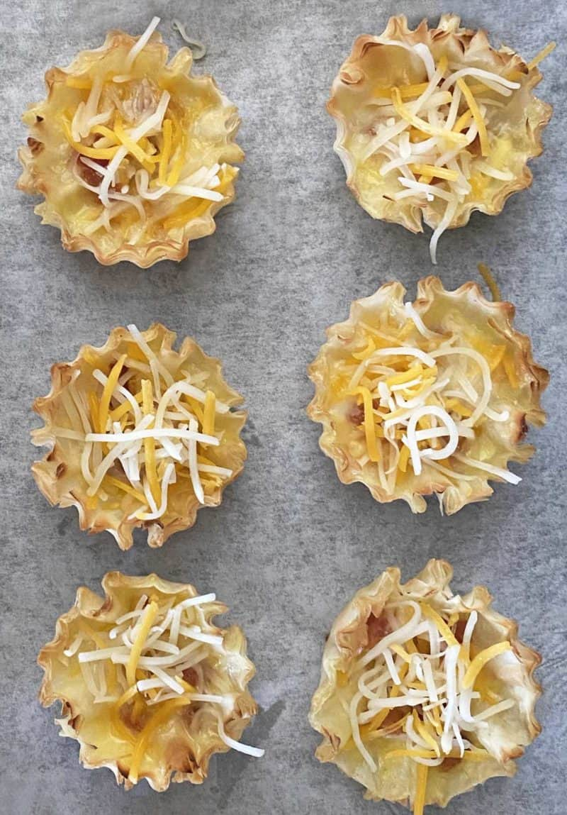 6 baked phyllo shells sprinkled with shredded cheese on a parchment lined baking sheet.