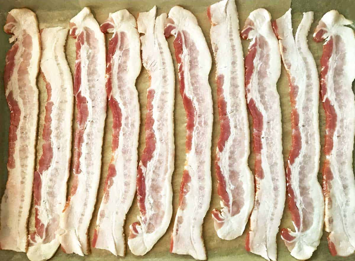 10 strips of bacon arranged on a parchment paper lined baking sheet.