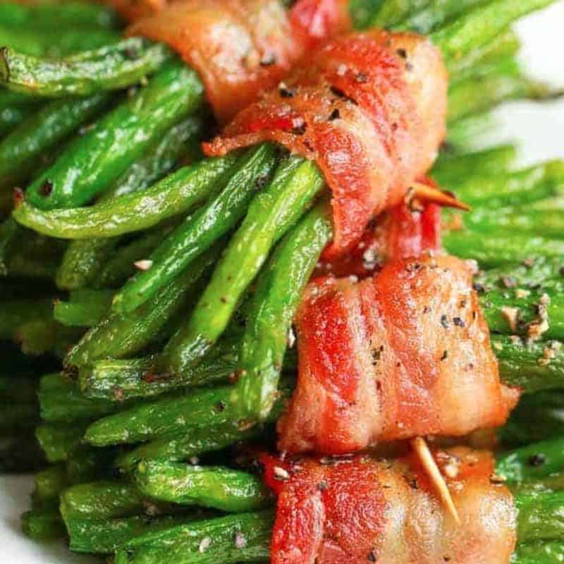 A close up of green beans with bacon side dish