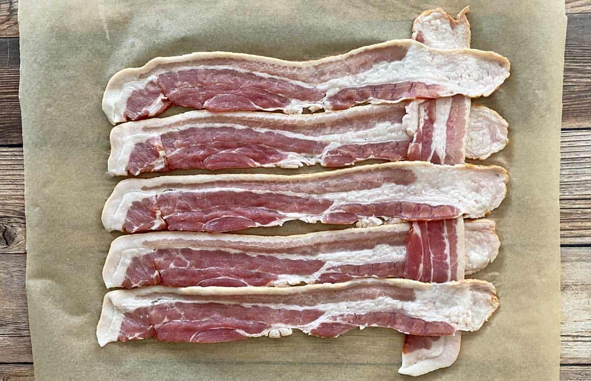 A process photo showing the first step of making a bacon weave, with seven strips of bacon on parchment paper.