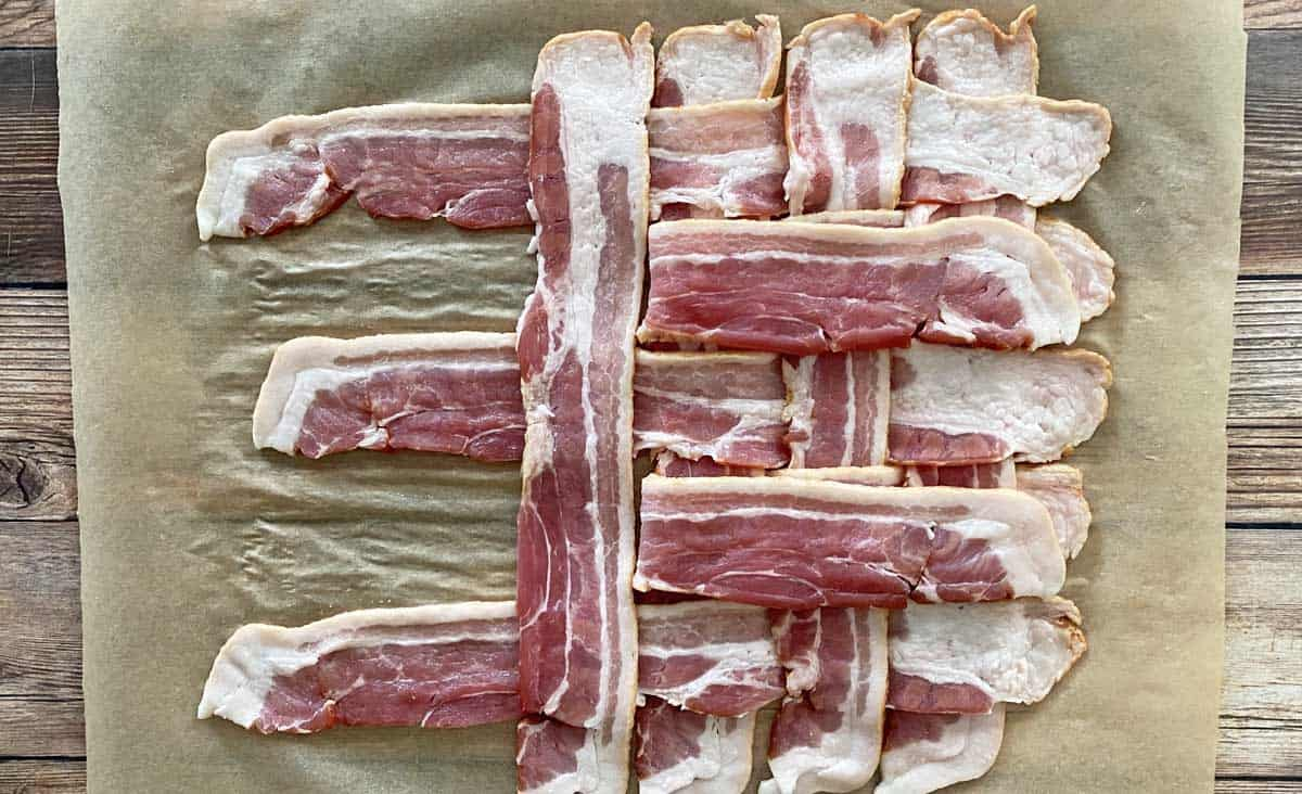 A process shot showing how to make a bacon weave, with half of the bacon slices woven together, on a piece of parchment paper.