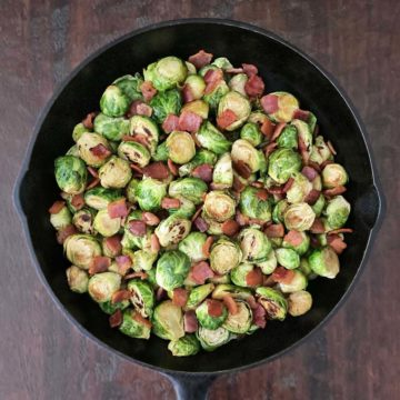 cast iron skillet filled with cooked Brussel sprouts with Bacon and Balsamic