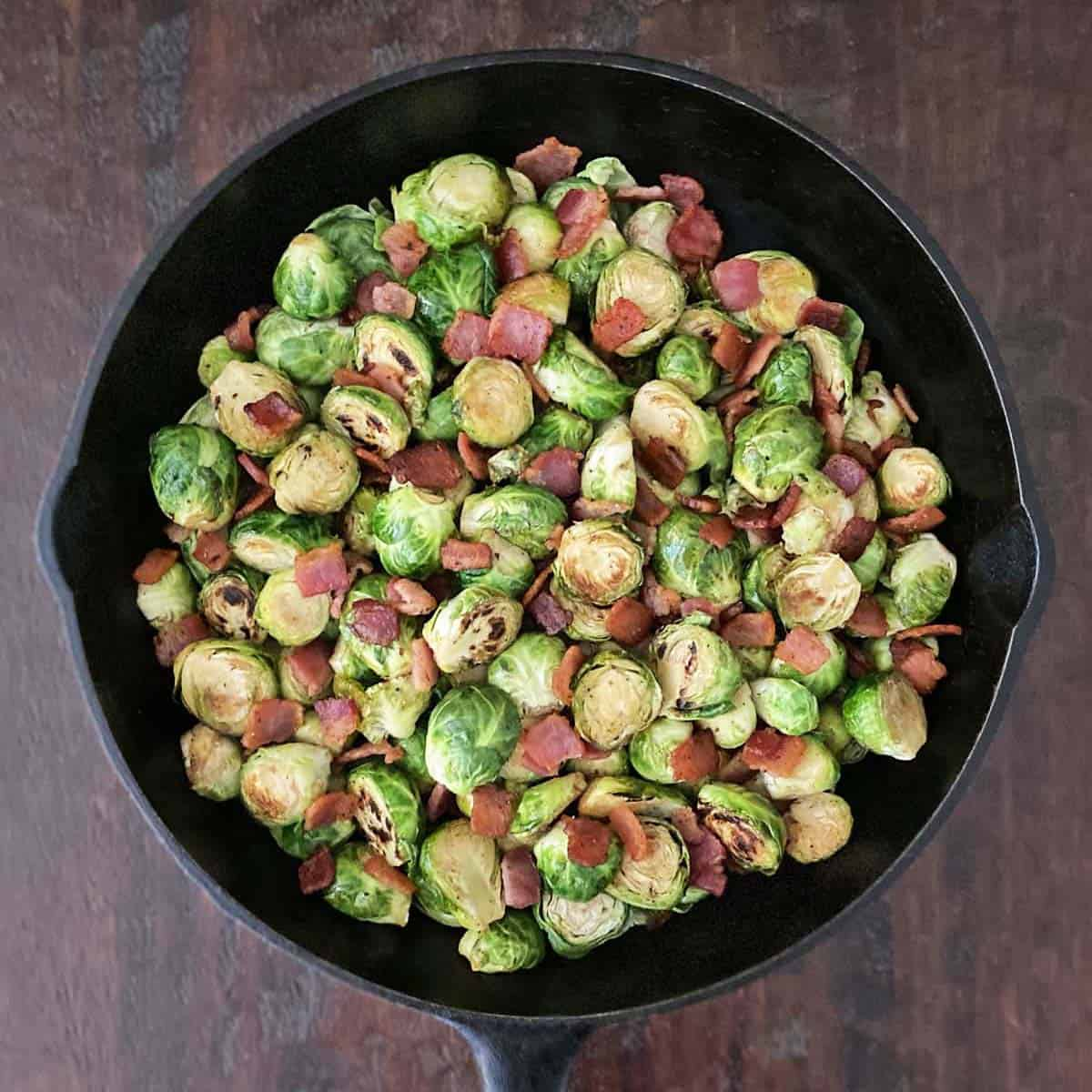 A cast iron skillet filled with fully cooked halved brussels sprouts and bacon on a wood background