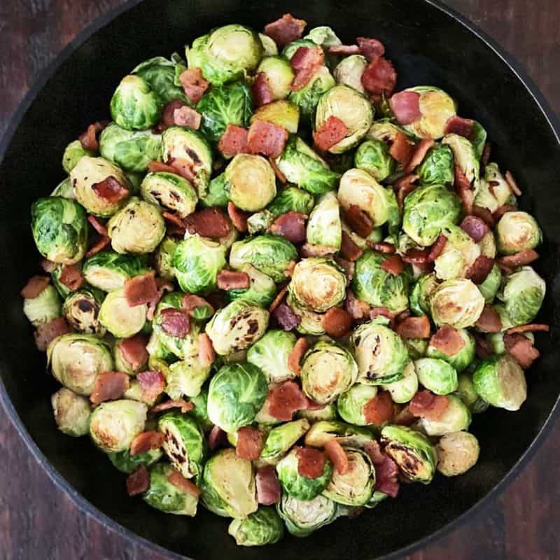 cooked brussel sprouts in a black cast iron skillet with bacon and balsamic
