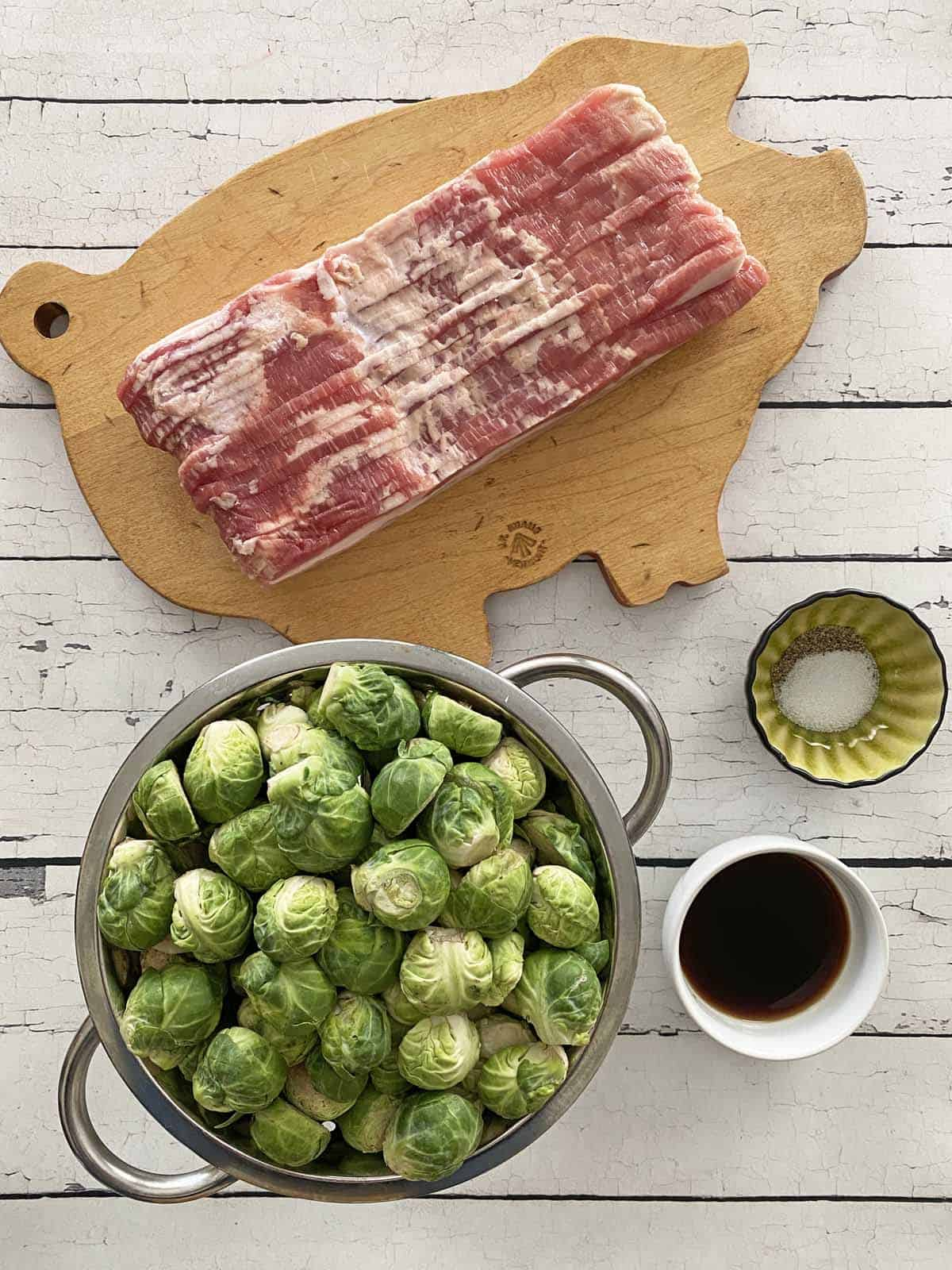 A wood cutting board with a pound of bacon, a collander full of Brussels sprouts, a dish of balsamic vinegar and a dish of salt and pepper
