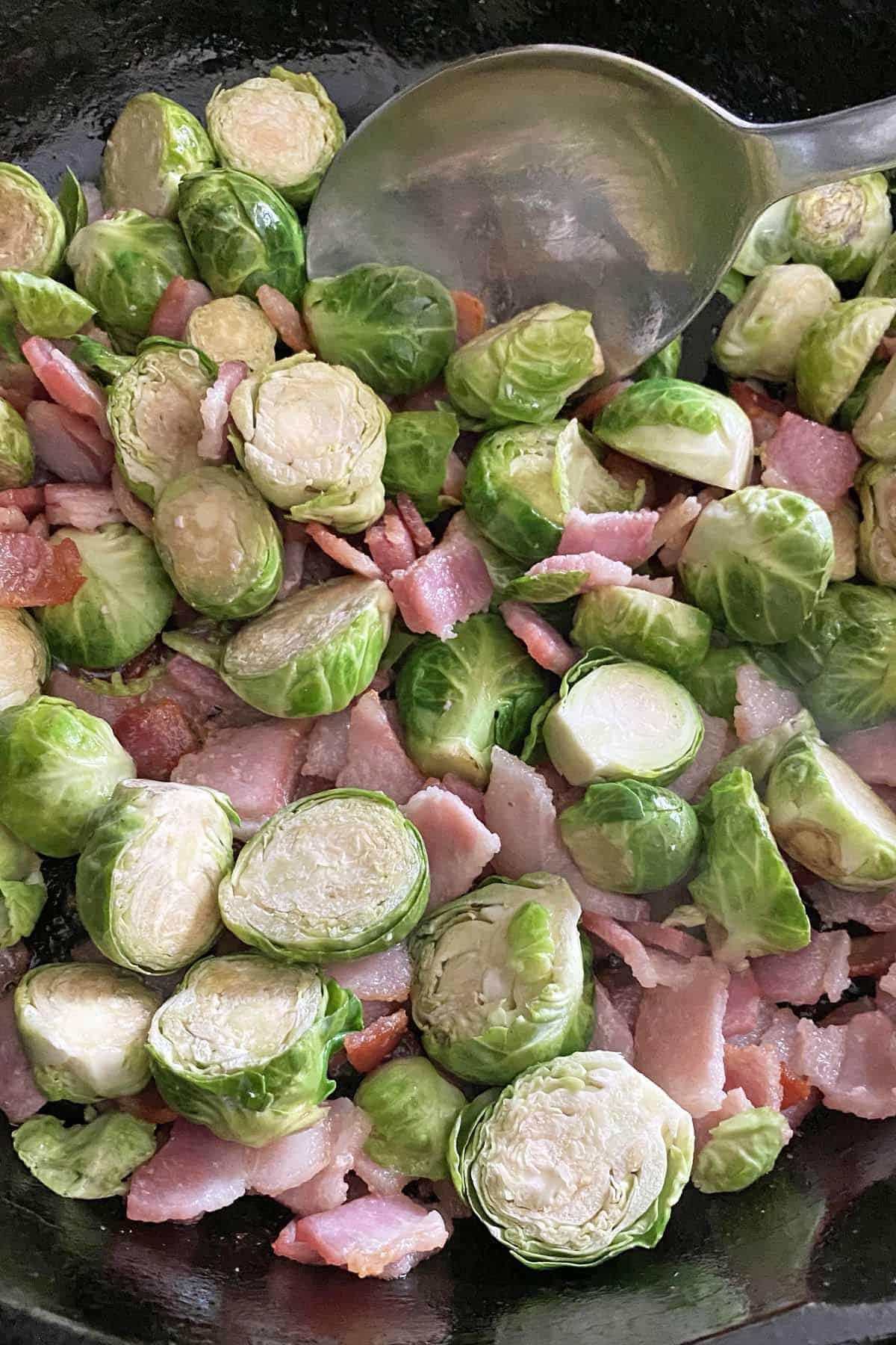 Partially cooked steamed Brussel sprouts with partially cooked bacon pieces in a skillet with a spoon