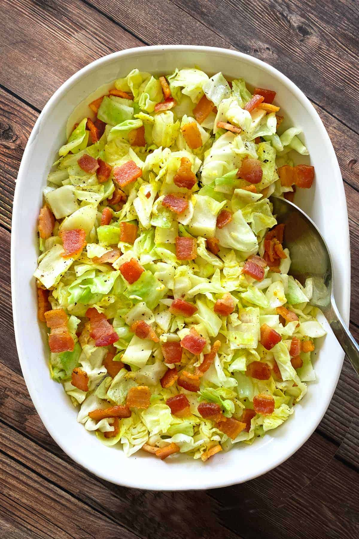 White oval serving dish filled with fried cabbage with bacon and garlic and a silver serving spoon.
