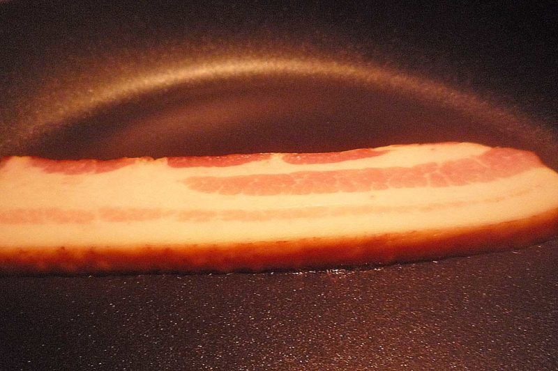 One thick slice of bacon in a black pan, just beginning to cook.