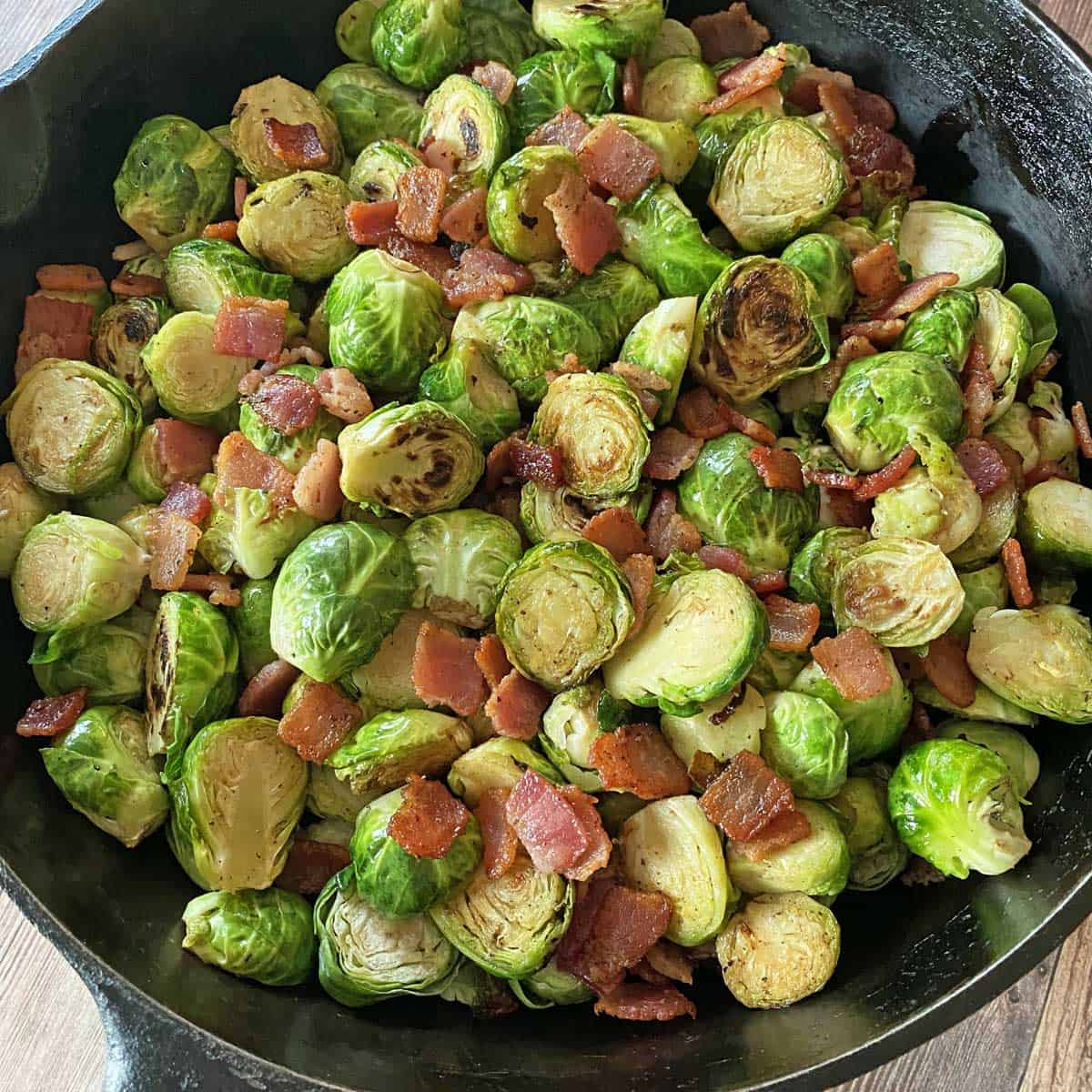 Cast iron skillet with finished Brussel sprouts with bacon, garlic and Balsamic, ready to serve.