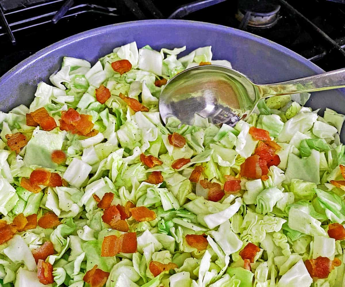 Close up of skillet with partially cooked cabbage and bacon.