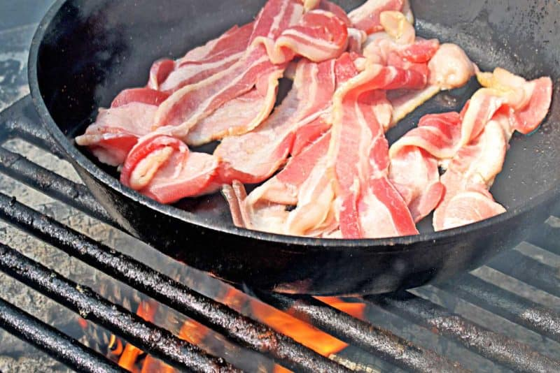 A pound of bacon slices cooking in a large cast iron skillet over a grill grate with fire beneath.