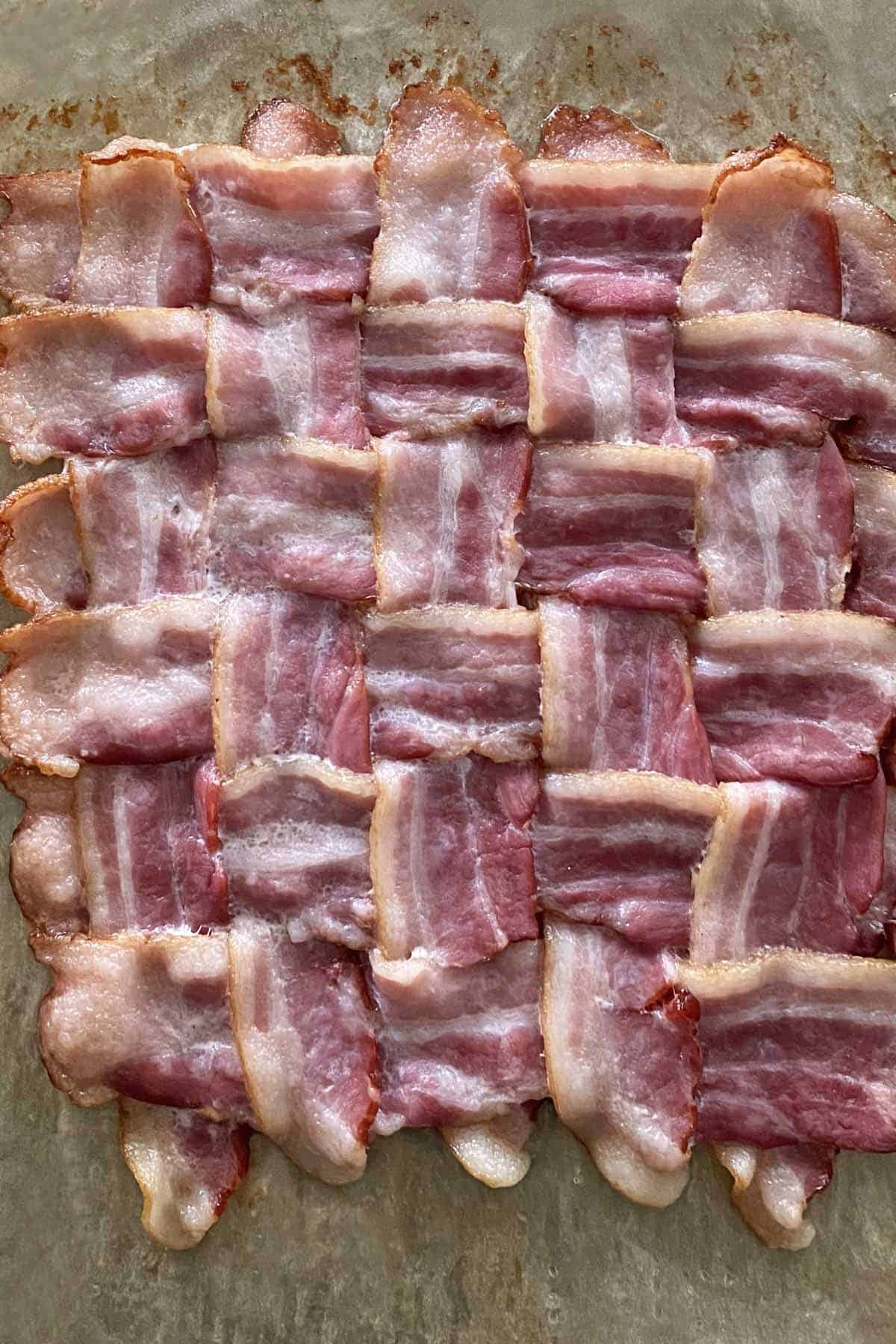 A close up of a partially cooked bacon weave on a piece of parchment paper