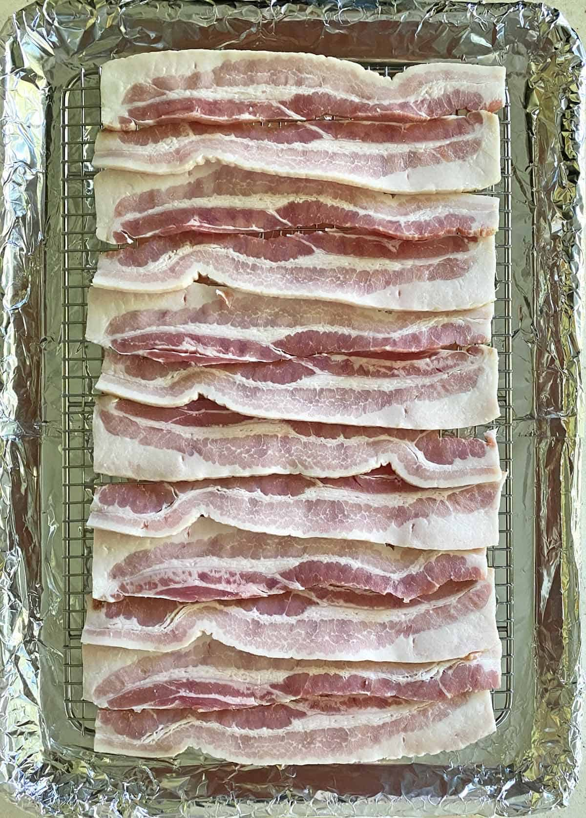 12 strips of thick cut bacon arranged on a baking rack placed on a foil wrapped baking sheet