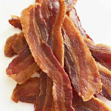 A dozen strips of homemade bacon jerky in a pile on a white background