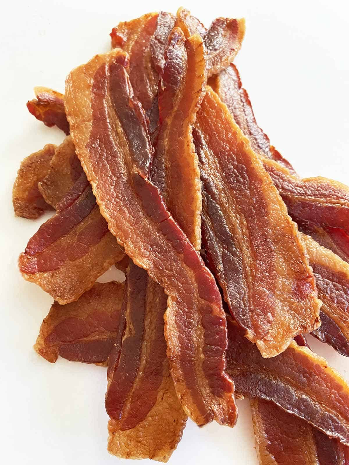 12 pieces of homemade bacon jerky in a pile, on a white background