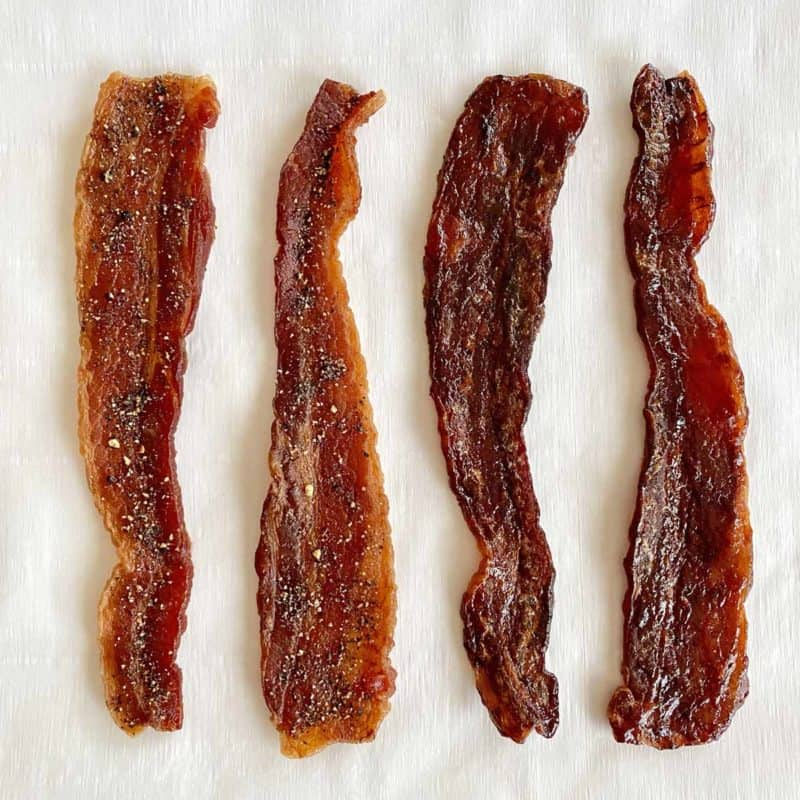Two strips of black pepper bacon jerky and two strips of barbecue bacon jerky on a piece of white parchment paper