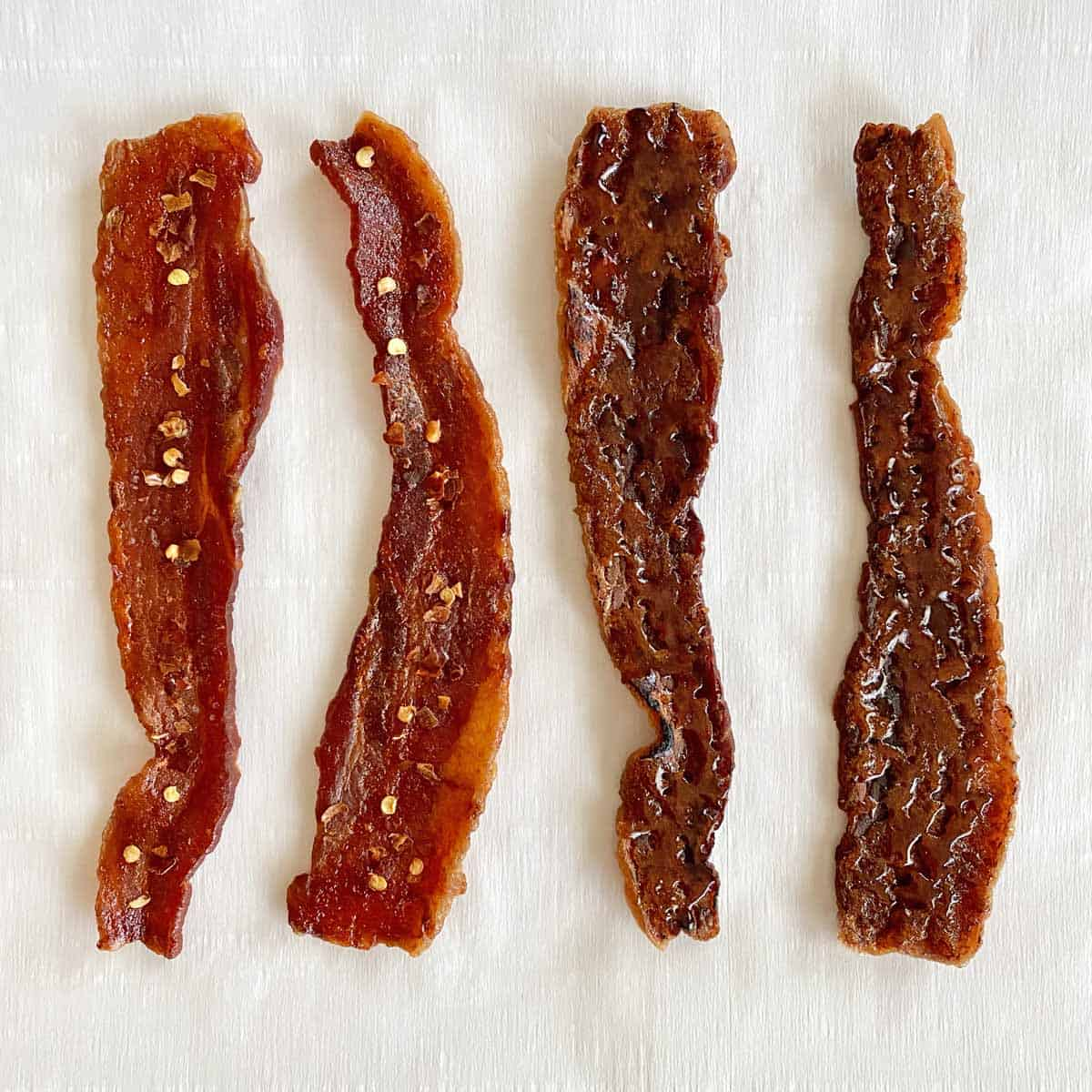 Two strips of sriracha bacon jerky and two strips of candy bacon jerky on a piece of white parchment paper